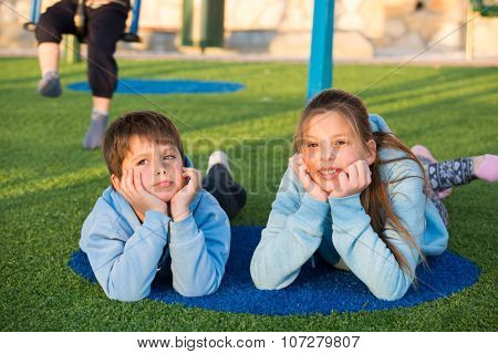 Adorable kids. Sister and brother in the same blue jackets play in the playground