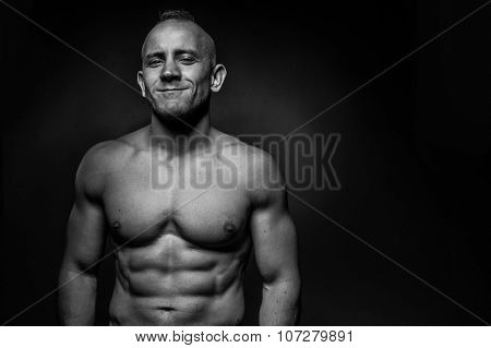 Shirtless attractive middle-aged muscular man with a lovely wide charismatic smile, upper body black and white portrait with copyspace