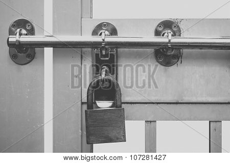 Metal padlock and metal door at factory