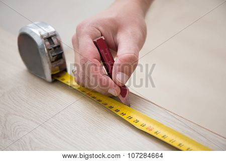 Male Hands With Measuring Tape And New Laminated Wooden Floor