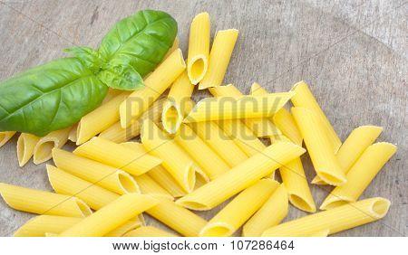 Fine penne noodles on wooden board