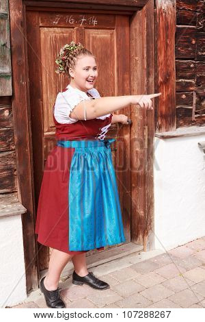 Bavarian overweight young woman in dirndl shows with finger on what.
