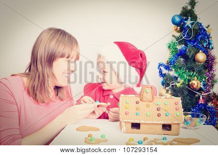mother and son decorating gingerbread house