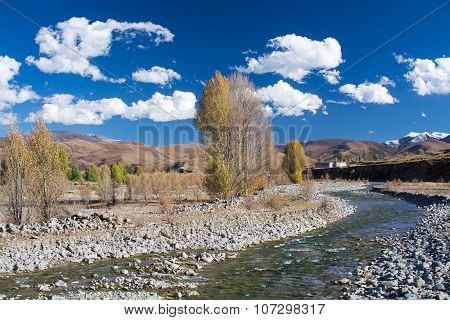 Brook With Trees In Autumn And Mountains With Blue Sky Background