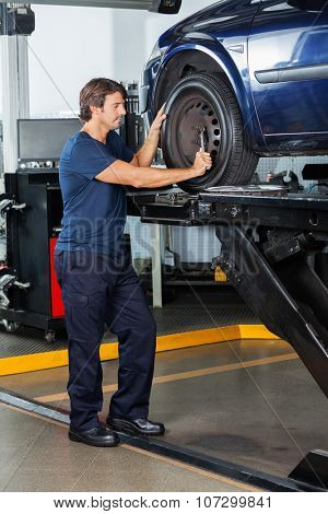 Male mechanic fixing lifted car tire at auto repair shop