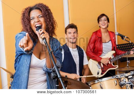 Passionate female singer pointing while performing in recording studio