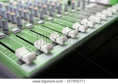Closeup of buttons on music mixer in recording studio
