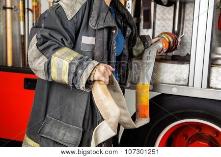 Midsection of firewoman adjusting water hose in truck at fire station