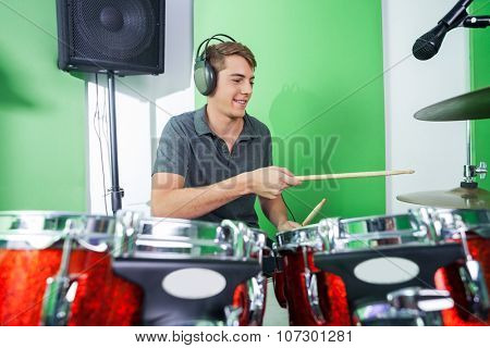 Smiling young male professional playing drums in recording studio