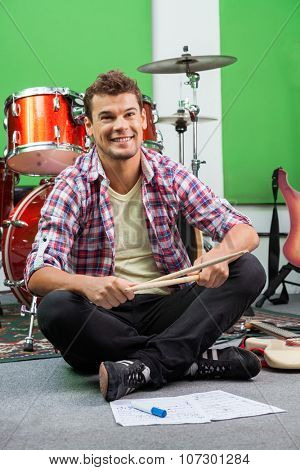 Happy male drummer holding sticks while sitting on floor at recording studio