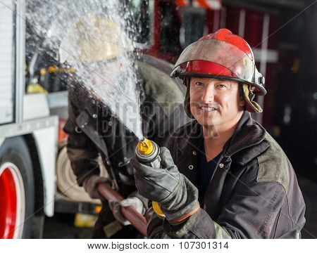 Confident male firefighter spraying water while practicing with colleague at fire station
