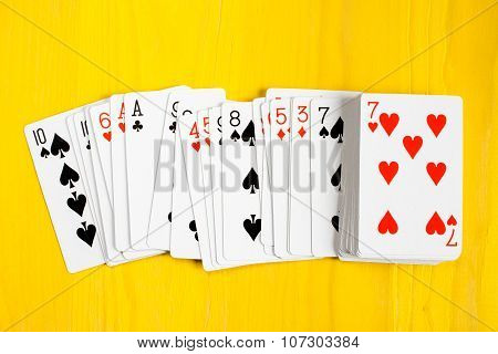 Playing Cards On Yellow Wooden Background