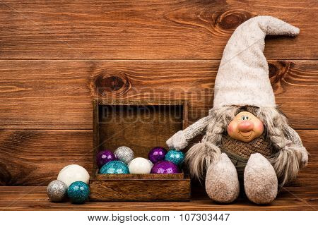 Christmas decorative gnome sitting near christmas balls on the wooden background.
