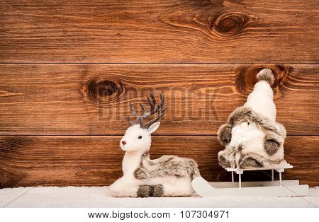 Christmas decorative toys (reindeer and gnome) with sled on the snowed surface on the wooden backgro