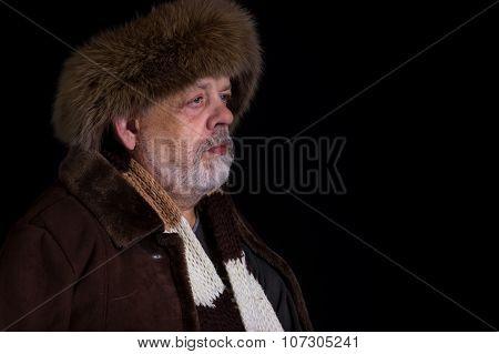 Portrait of tough senior man in winter clothes in studio
