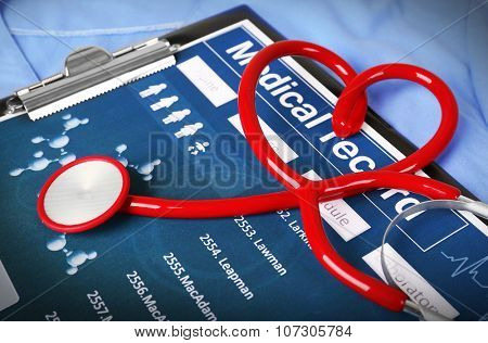 Red heart shaped stethoscope with medical record on blue uniform, close up