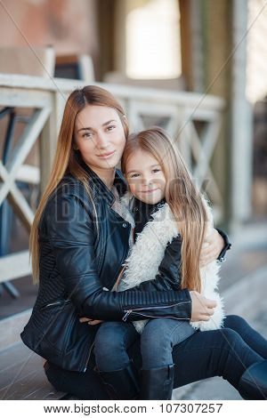 Autumn portrait of stylish mums and daughters