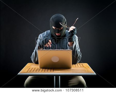 Hacker at work, holding glasses in the hand