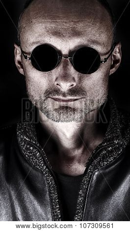 Stylized portrait of a middle-aged man in dark glasses