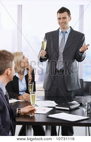 Happy Businessman Raising Toast At Office