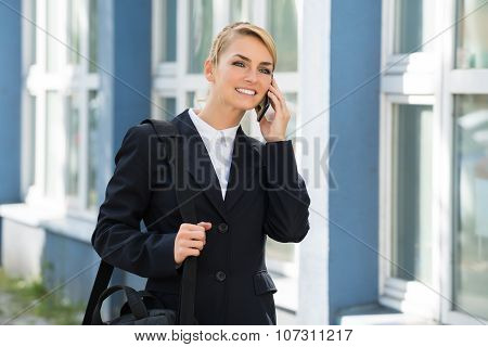 Businesswoman Using Cell Phone While Carrying Briefcase