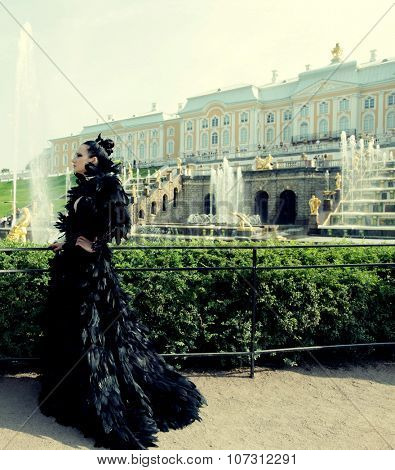 Princess in the park next to the fountain and palace