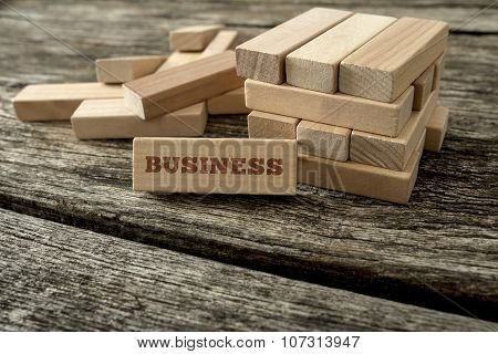 Word Business Written On A Wooden Peg Leaning On A Structure Build Of Many Blocks