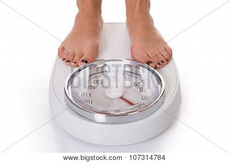 Low Section Of Woman Standing On Weighing Scale