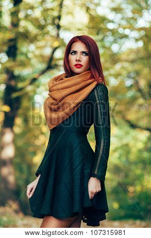 Attractive Red-haired Woman In A Green Dress Posing In The Park