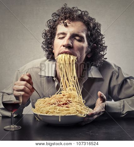 Hungry man eating pasta