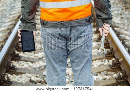 Railway employee with adjustable wrench and tablet PC on railway