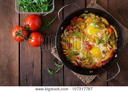 Fried eggs with vegetables in a frying pan on a wooden background