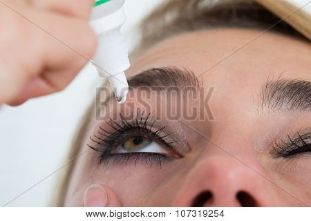 Woman Applying Eye Drop Over White Background