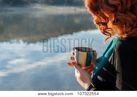 red-haired girl  holding in her hands a cup from the thermos