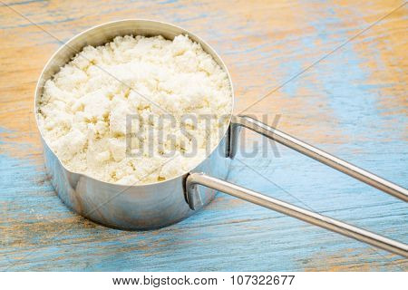 measuring metal scoop of whey protein powder against wood background