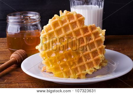 homemade waffles with honey and milk on a dark wooden background