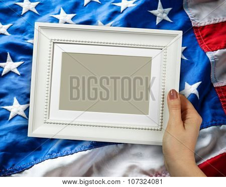 Wooden frame in beautiful woman hands on the background of flapping flag USA with wave
