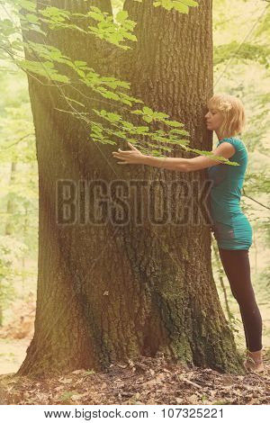 Young woman hugging the tree in forest. Post processed with vintage faded filter and sun flare.