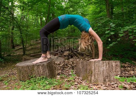 Young woman practicing yoga bridge pose in forest.