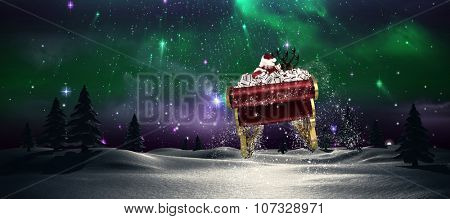 Santa flying his sleigh against aurora shimmering in night sky