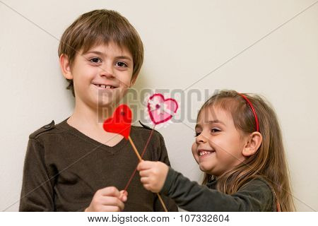 Little Girl And Boy With Red Hearts