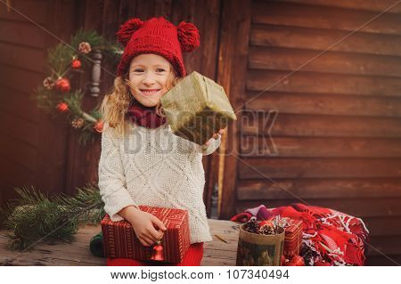 happy child girl in knitted red hat and white sweater celebrating christmas outdoor at cozy wooden c