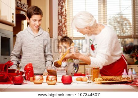 Grandmother With Grandchilds In Kitchen, Christmas.
