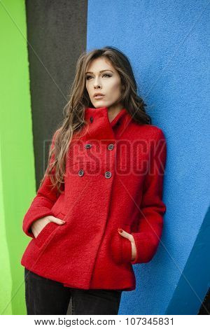 young woman in red coat  lean on blue wall, outdoor shot