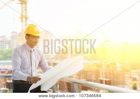 Asian Indian male site contractor engineer with hard hat holding blue print paper inspecting at construction site, crane at the background.