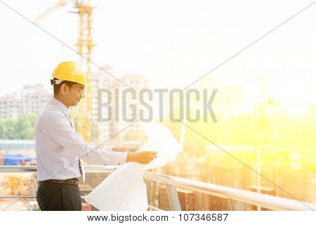 Asian Indian male site contractor engineer with hard hat holding blue print paper inspecting at construction site, crane with sunlight at the background.