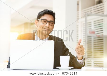 Asian Indian business people using a laptop thumb up at cafe. India male business man, modern building with beautiful golden sunlight as background.