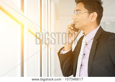 Indian estate agent checking on new office to let and calling on phone.