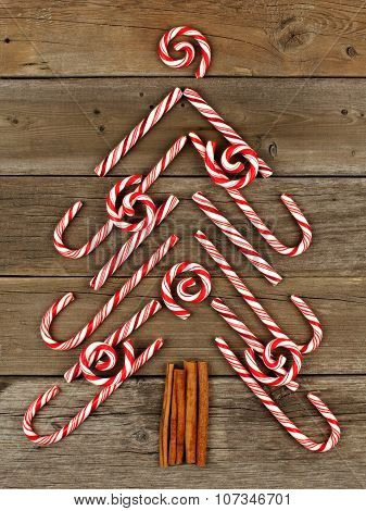 Christmas tree of candy canes and peppermint swirls over wood