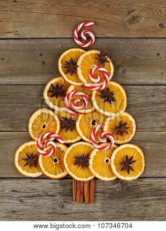 Christmas tree of orange slices and peppermint swirls over wood